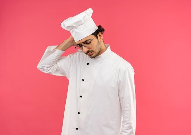 Guardando giù triste giovane cuoco maschio che indossa l'uniforme dello chef e bicchieri mettendo la mano sulla testa