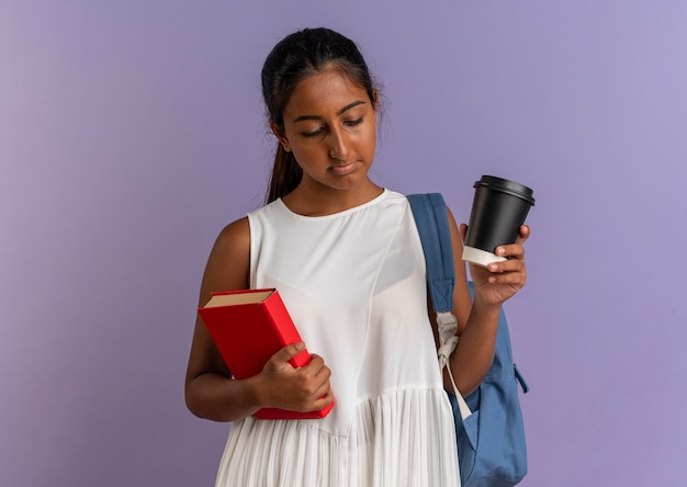 Guardando verso il basso la giovane studentessa che indossa la borsa con la schiena che tiene il libro e la tazza di caffè su sfondo viola