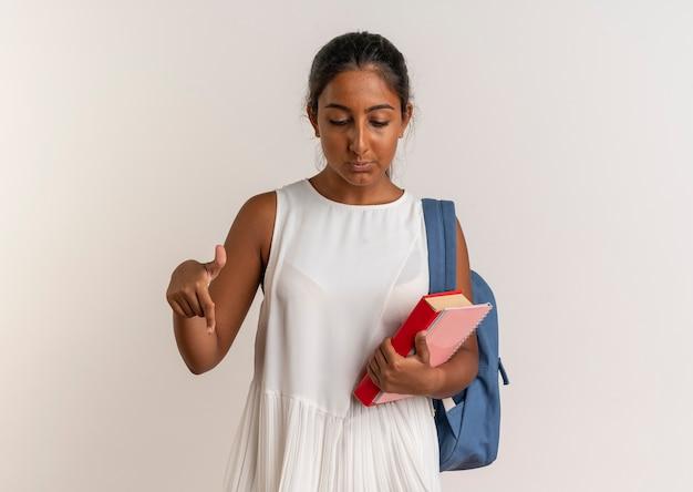 Guardando verso il basso giovane studentessa che indossa uno zaino tenendo il libro con il taccuino e punti in basso