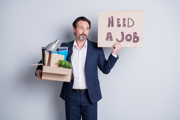 일자리를 찾고. 불행한 노동자 성숙한 남자 금융 위기 잃어버린 직장 보류 판지 상자 소지품 종료 보류 현수막 배너 검색 직장 착용 정장 고립 된 회색 배경의 사진