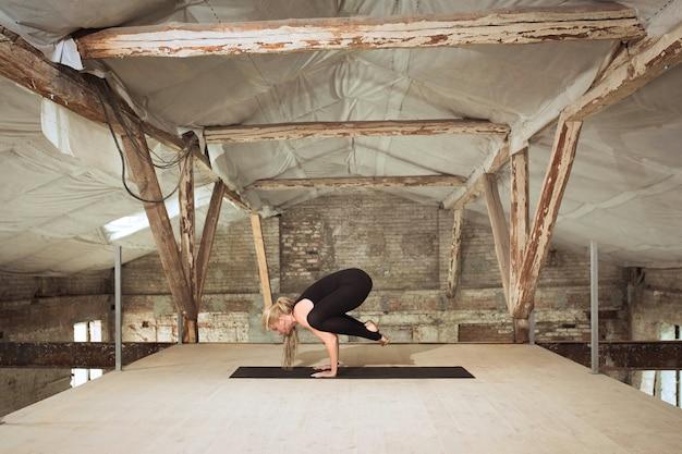 찾고있는. 젊은 체육 여자 버려진 된 건설 건물에 요가 연습. 정신적 및 신체적 건강 균형. 건강한 라이프 스타일, 스포츠, 활동, 체중 감소, 집중력의 개념.