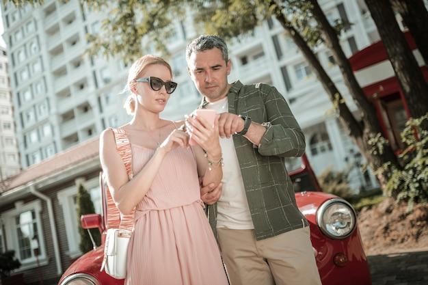 조언을 구합니다. 스마트폰으로 인터넷에서 차에 대한 정보를 검색하는 남편과 아내.