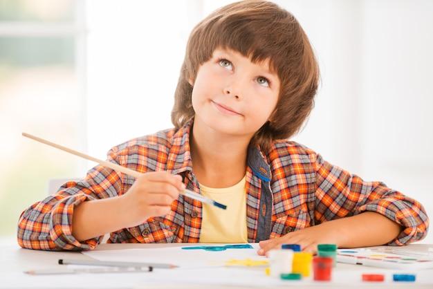 Ищу вдохновение. милый маленький мальчик расслабляется во время рисования акварелью, сидя за столом