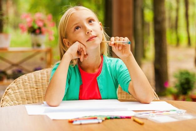 インスピレーションを探しています。あごに手をつないで、色とりどりの鉛筆と紙を置いてテーブルに座って目をそらしている思いやりのある少女
