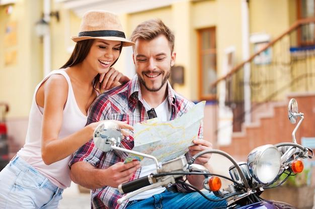 行く場所を探しています。一緒にスクーターに座って、女性がそれを指して笑っている間地図を調べる美しい若い愛情のあるカップル