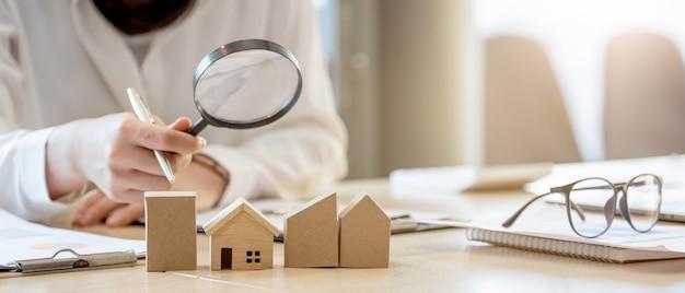 Ищу агентство недвижимости, страхование имущества, ипотечный кредит или новый дом. женщина с увеличительным стеклом над деревянным домом в ее офисе.
