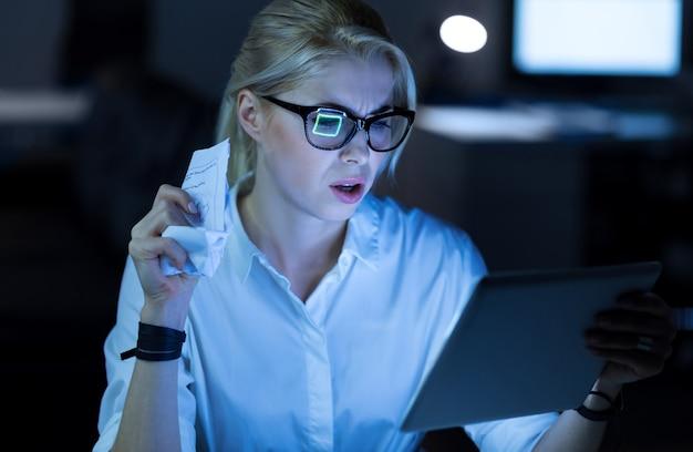 올바른 솔루션을 찾고 있습니다. 사무실에 앉아서 프로젝트를 진행하는 동안 태블릿을 사용하는 심각한 집중 it 여성