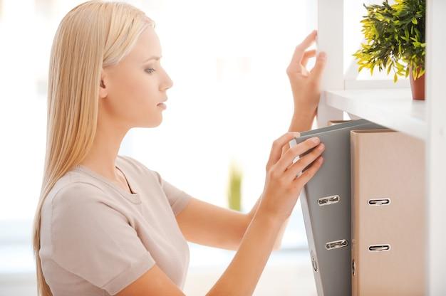 그 문서를 찾고 있습니다. 사무실에서 자기 근처에 서 있는 동안 필요한 문서를 찾고 있는 아름다운 젊은 여성의 측면