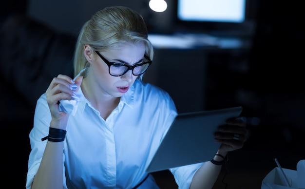 최고의 아이디어를 찾고 있습니다. 사무실에 앉아서 프로젝트를 진행하는 동안 태블릿을 사용하는 세심한 집중 it 여성