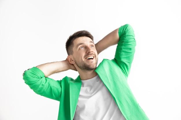 Ищем лучший момент. молодой мечтательный улыбающийся человек ждет шанзы, изолированные на сером фоне. мечтатель в студии в белой футболке
