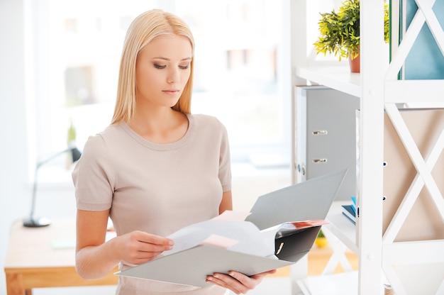 올바른 문서를 찾고 있습니다. 사무실 선반 근처에 서서 문서를 검토하는 아름다운 젊은 여성