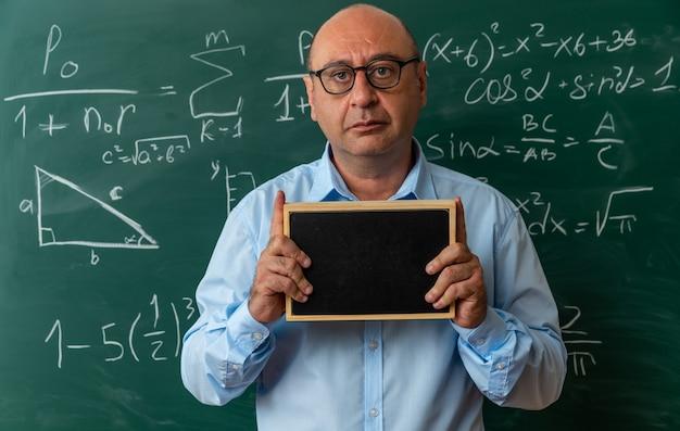 Guardando davanti insegnante maschio di mezza età con gli occhiali in piedi davanti alla lavagna con in mano una mini lavagna