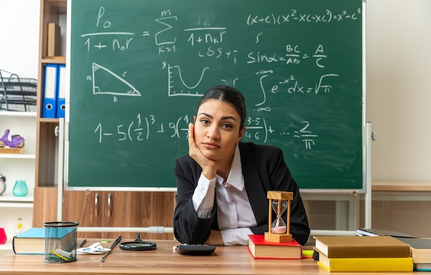 Guardando davanti la giovane insegnante femminile si siede al tavolo con materiale scolastico mettendo la mano sul mento in classe