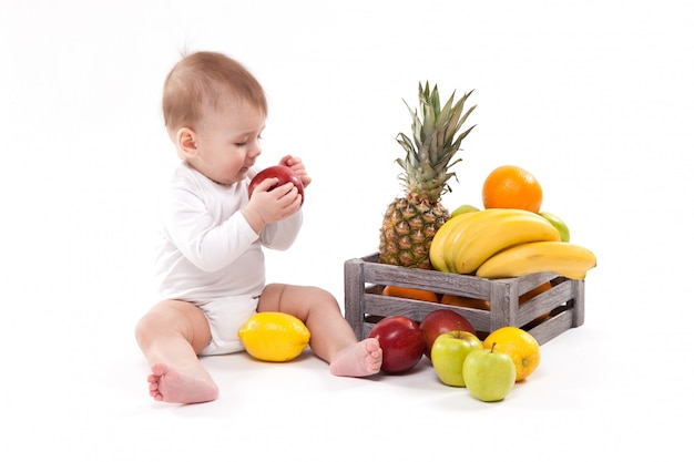 Looking at fruit cute smiling baby on white  among fru