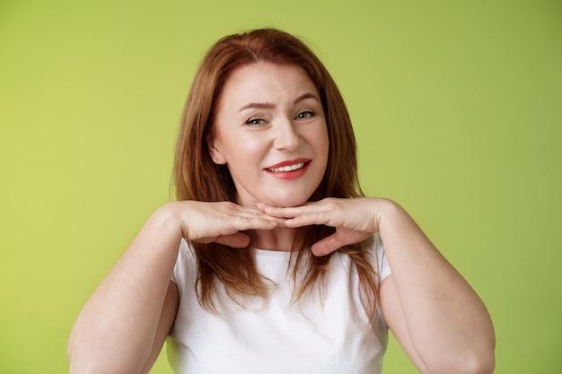 Guardando bene felice allegra rossa donna di mezza età sorridente felice tenere le mani sotto il mento accettare difetti impura come la propria condizione della pelle applicare invecchiamento creme cosmetici muro verde