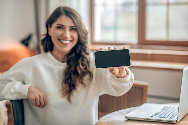 幸せそうに見えます。スマートフォンを持って幸せそうに見える白いブラウスを着た格好良い若い女性
