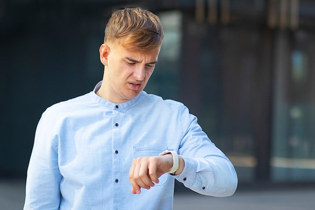 Looking at his watch on his hand, formally dressed in a white shirt. headache or fever in a man.