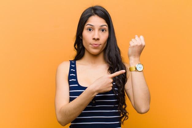 せっかちで怒っているように見え、時計を指さし、時間厳守を求め、時間通りになりたい
