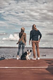Смотрю в одном направлении. полная длина вид сзади красивой молодой пары, стоящей со своей собакой на берегу реки, проводя время на открытом воздухе