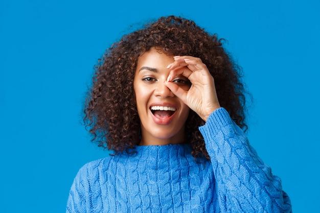 Глядя вдаль. крупным планом веселая привлекательная афро-американская женщина что-то ищет, нашла отличную праздничную скидку, просматривает знак хорошо и довольна улыбкой, синяя стена.