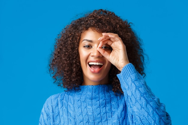 Looking into distance. close-up cheerful attractive african-american woman searching something, found great holidays discount, look through okay sign and smiling pleased, blue wall.