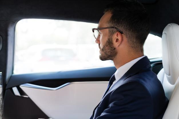 鏡をのぞき込む。車の後部座席に座って鏡を見ているひげを生やした実業家