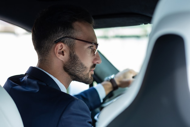 鏡をのぞき込む。運転中に右側のミラーを見ている眼鏡をかけているひげを生やした男