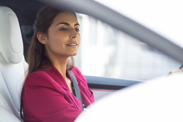 거울을 찾고. 차 안에서 백미러를 들여다보는 아름다운 검은 머리의 젊은 여성 사업가
