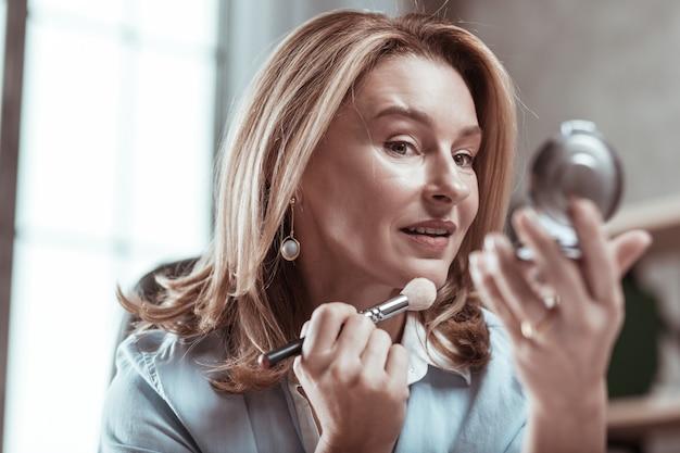 鏡を見ています。鏡を見るスタイリッシュなイヤリングを着た黒い瞳の女性の接写