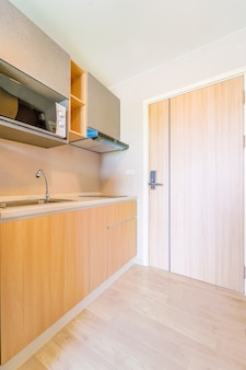 Looking into a small empty kitchen with stove, fridge and cupboards