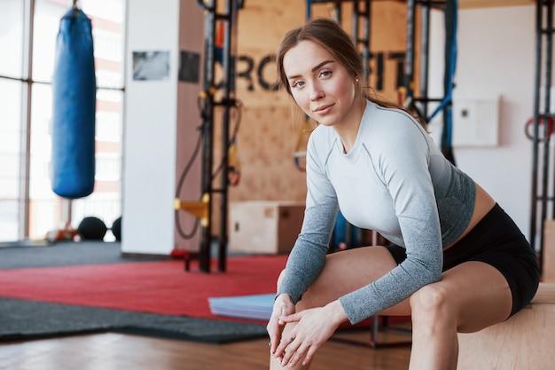 Смотрю в камеру. спортивная молодая женщина имеет фитнес-день в тренажерном зале в утреннее время