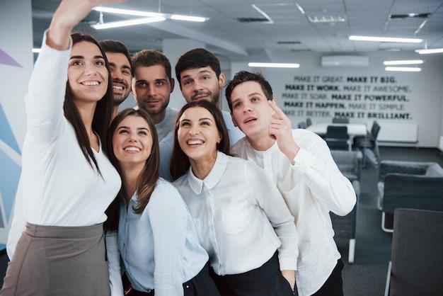 カメラを見ています。現代の良い明るいオフィスでクラシックな服でselfieを作る若いチーム