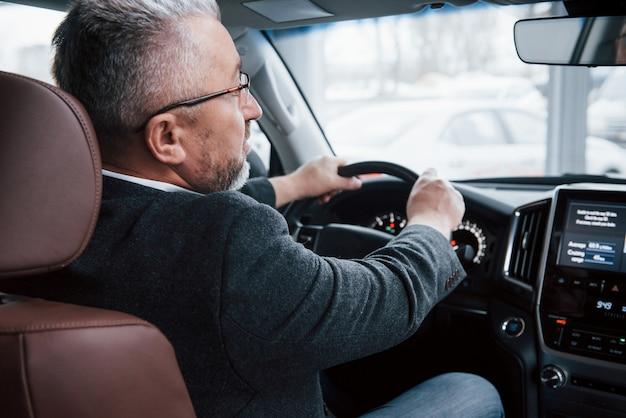フロントミラーをのぞき込む。現代の新しい車を運転する公式の服の上級ビジネスマンの後ろからの眺め