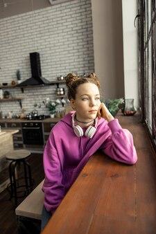 Looking into window. green-eyed teenage girl wearing pink sweatshirt looking into window at home