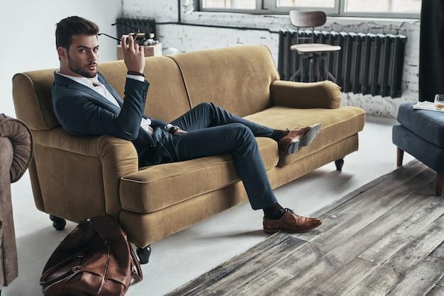 あなたの心をのぞき込む。アイウェアを保持し、ソファに座ってカメラを見てフルスーツのハンサムな若い男
