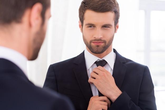 Выглядит просто идеально. красивый молодой человек в строгой одежде поправляет галстук и улыбается, стоя у зеркала