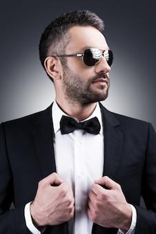 完璧に見えます。灰色の背景に立っている間目をそらしている正装とサングラスのハンサムな成熟した男の肖像画