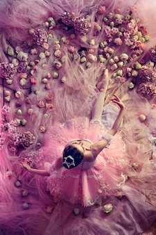 Looking for love. top view of beautiful young woman in pink ballet tutu surrounded by flowers. spring mood and tenderness in coral light. art photo. concept of spring, blossom and nature's awakening.