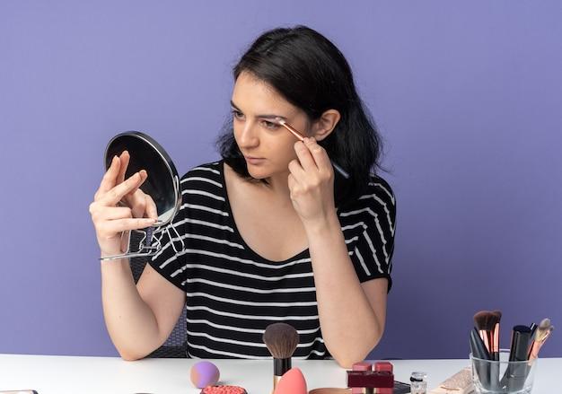Guardando lo specchio felice dall'aspetto giovane bella ragazza si siede al tavolo con strumenti per il trucco applicando ombretto con pennello per il trucco isolato sulla parete blu