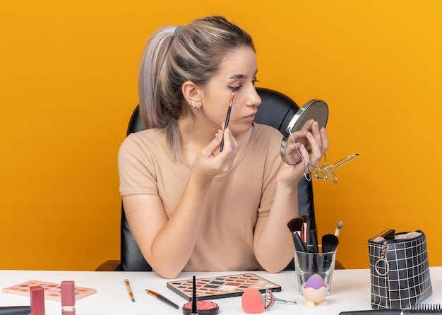 Guardando lo specchio la giovane bella ragazza si siede al tavolo con gli strumenti per il trucco applicando l'ombretto con il pennello isolato sul muro arancione