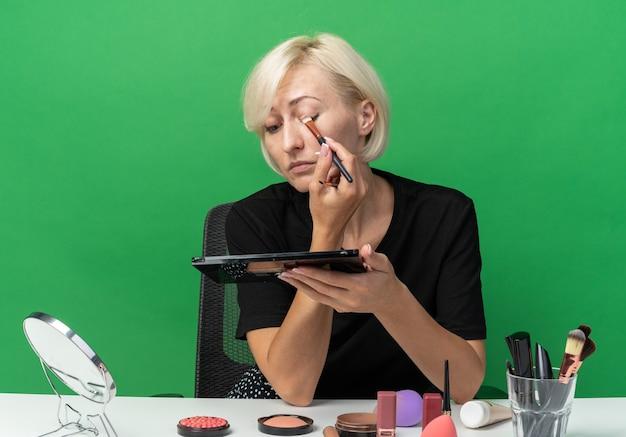 Guardando lo specchio la giovane bella ragazza si siede al tavolo con gli strumenti per il trucco applicando l'ombretto con il pennello per il trucco isolato sul muro verde green