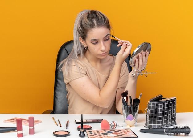 Guardando lo specchio la giovane bella ragazza si siede al tavolo con gli strumenti per il trucco applicando l'ombretto con il pennello per il trucco isolato sul muro arancione orange