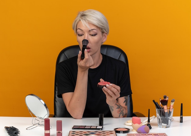 Guardando lo specchio la giovane bella ragazza si siede al tavolo con gli strumenti per il trucco applicando il fard in polvere con il pennello in polvere isolato sul muro arancione orange