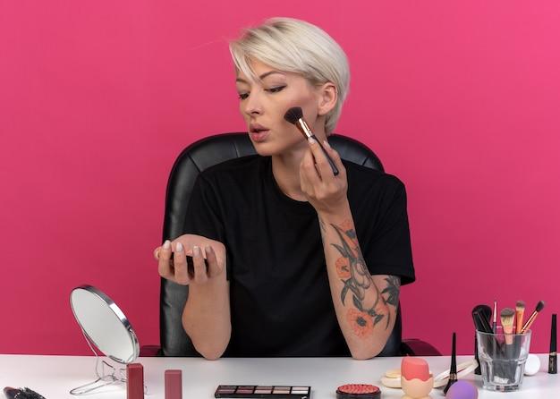 Guardando lo specchio la giovane bella ragazza si siede al tavolo con gli strumenti per il trucco applicando il fard in polvere con il pennello in polvere isolato sul muro rosa pink