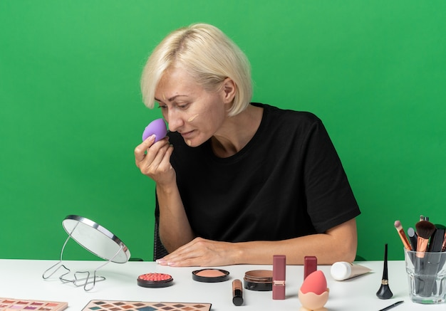 Guardando lo specchio la giovane bella ragazza si siede al tavolo con gli strumenti per il trucco applicando la crema tonificante con la spugna isolata sul muro verde
