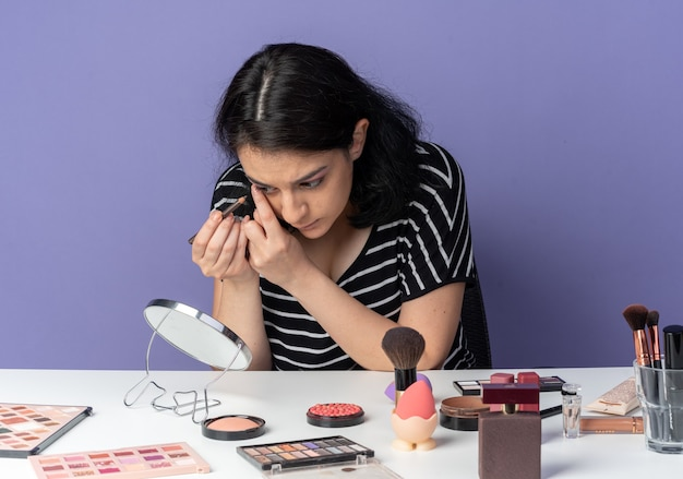 Guardando lo specchio, la giovane bella ragazza si siede al tavolo con gli strumenti per il trucco disegna la freccia con l'eyeliner isolato sul muro blu