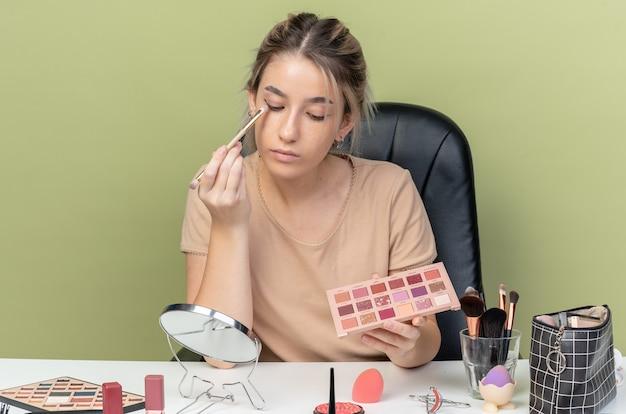Guardando lo specchio giovane bella ragazza seduta alla scrivania con strumenti per il trucco che applica ombretto con pennello per il trucco isolato sul muro verde oliva