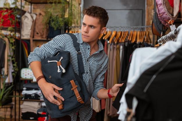 긴장 해 보인다. 배낭을 들고 옷을 훔치는 것에 대해 생각하면서 긴장된 감정적 인 젊은이