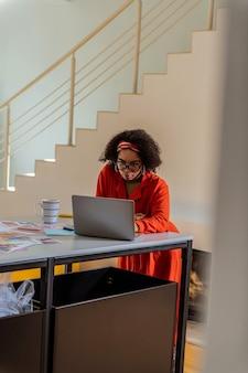 화면을보고 있습니다. 이상한 안경과 빨간 옷을 입고 직장에서 시간을 보내는 바쁜 매력적인 혼혈 여성