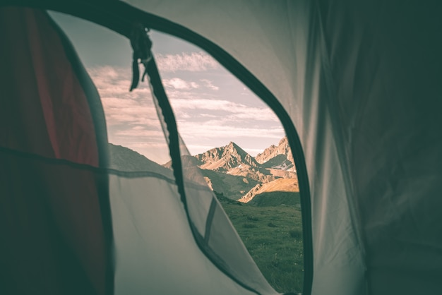 Looking out the mountain landscape at sunrise from interior of camping tent.